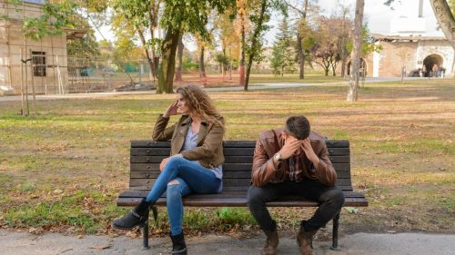 a couple sitting on a bench not talking to each other