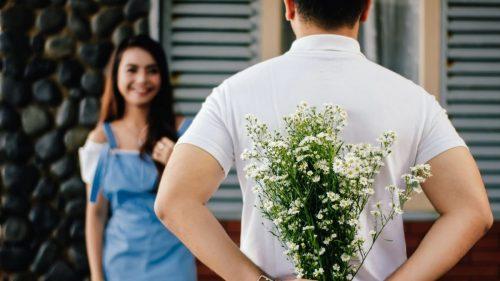 guy holding flowers for the girl