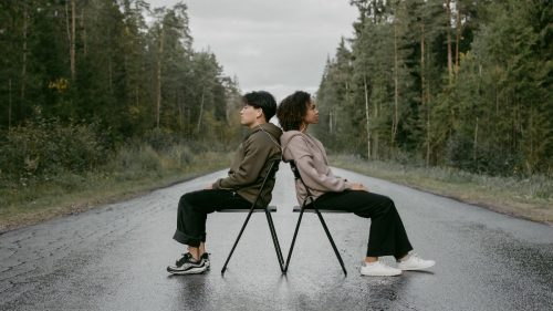 a man and woman sitting on chair with their back touching