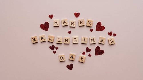 happy valentines day text on pink surface