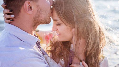 boy kissing his girlfriend's forehead