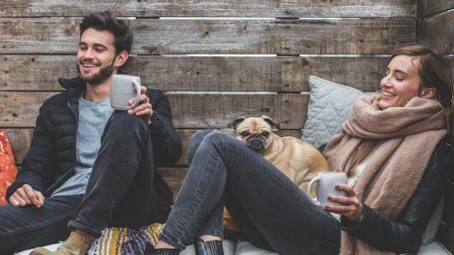 happy couple enjoying coffee with their dog
